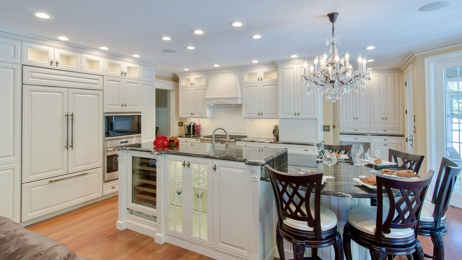An ornate white kitchen with an island, glass cabinets and wine storage.
