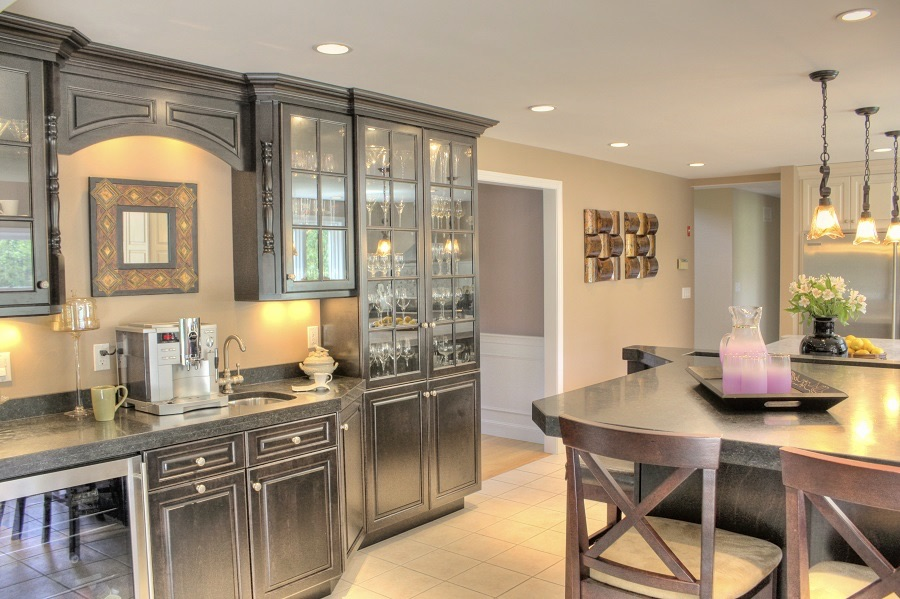 This elegant ornate kitchen features glass cabinets, a beverage fridge, island seating and hanging pendant lights