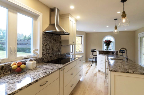 An exciting backsplash contrasts the white cabinets. The kitchen island is installed directly across the stove to improve function.