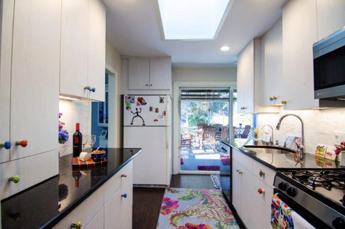 A large kitchen with stainless steel appliances. Colorful knobs makes a playful splash!