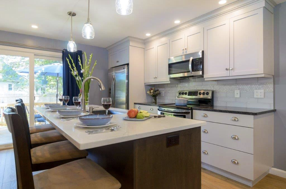 The Two Toned Kitchen makes a bold statement by contrasting white cabinets with a dark brown island.