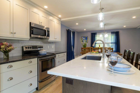 Two Tone Kitchens make a bold visual statement. White cabinets contrast black granite whereas the island features white granite against dark brown drawers. Clean crisp lines accent this kitchen. A sink installed in the island creates additional prep space by the oven and stove.