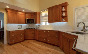 Warm wood cabinets create a relaxing atmosphere. Recessed lighting accents this kitchen by creating the perfect mood.